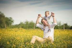 Baby sitting on fathers shoulders in a field of buttercups, Gloucestershire Photographer