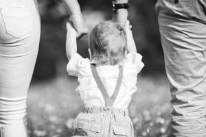 Toddler learning to walk by holding parents hands, Gloucestershire Photographer