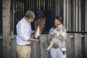 Family feeding bay mare, Gloucestershire Photographer